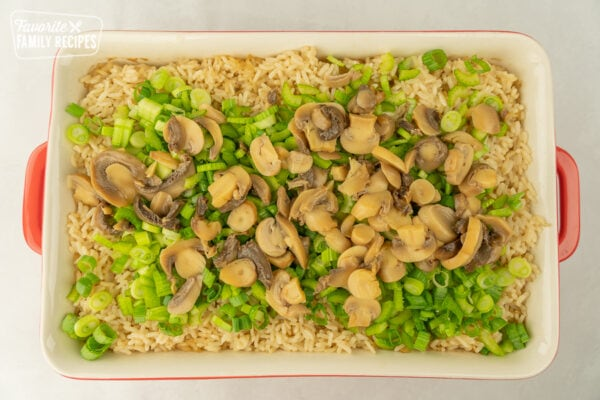 Rice with celery, green onions, mushrooms, and almonds in a large casserole dish.
