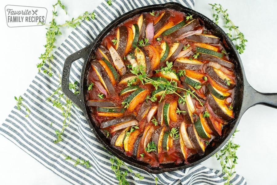 Ratatouille in a cast iron pan with a black and white striped napkin