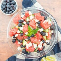 Watermelon feta salad in a glass bowl with a bowl of blueberries and limes