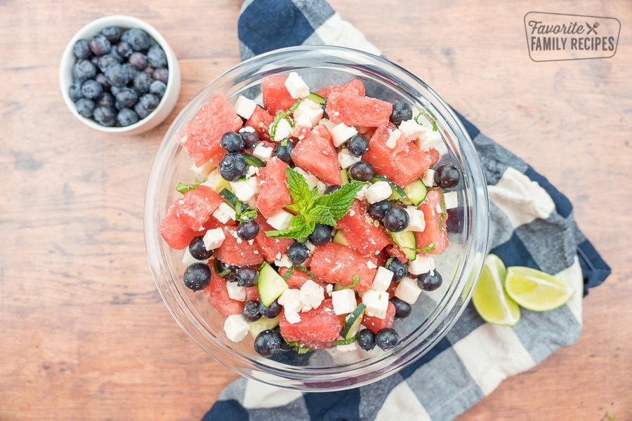 Watermelon feta salad in a glass bowl with limes and a bowl of blueberries