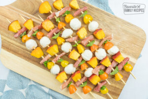 caprese salad skewers on a wooden cutting board