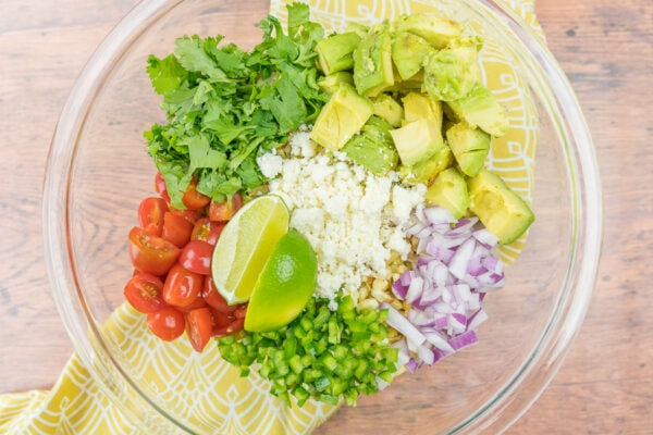 Bowl full of grilled corn, tomatoes, jalapenos, cilantro, cotija, avocado, and red onion.