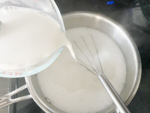 cornstarch mixture being poured into coconut mixture to make haupia