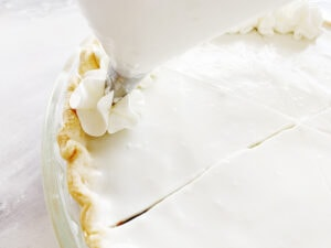 Piping whipped cream onto haupia pie
