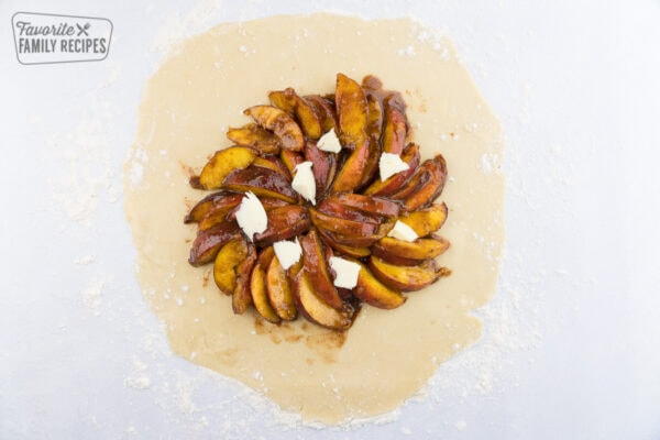 Spiced peaches on a pie crust, topped with chunks of butter