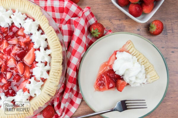 a slice of fresh strawberry pie on a plate topped with whipped cream