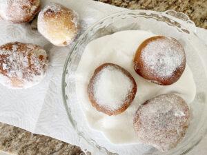 malasadas being rolled in sugar