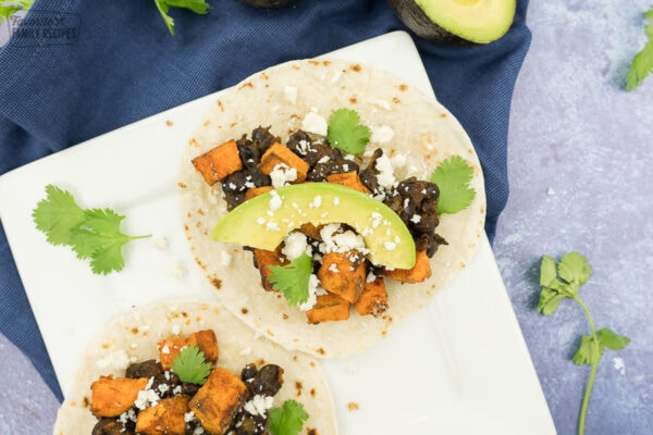 A taco with sweet potatoes, black beans, avocado, cilantro, and cotija cheese