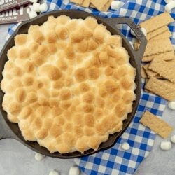 S'mores dip in a cast iron skillet surrounded by graham crackers, mini marshmallows, and hershey's bars