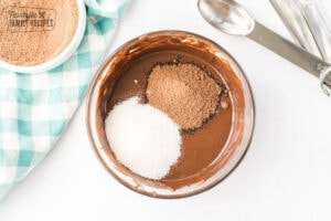 Sugar and hot cocoa mix added to melted chocolate in a glass bowl