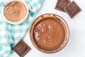 Milk, melted chocolate, sugar, and cocoa mix stirred together in a glass bowl
