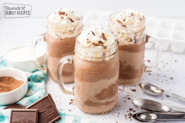 Three mugs of frozen hot chocolate topped with whipped cream and chocolate shavings