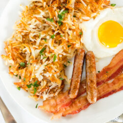 Cooked hash browns on a breakfast plate with bacon, eggs, and sausage