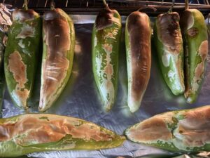 Chiles on a pan being roasted under a broiler