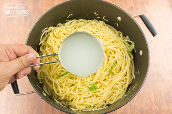 A measuring cup full of pasta water over a pot of pasta