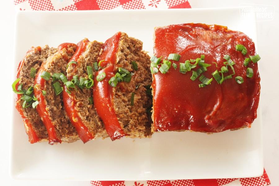 Sliced meatloaf on a platter with glaze