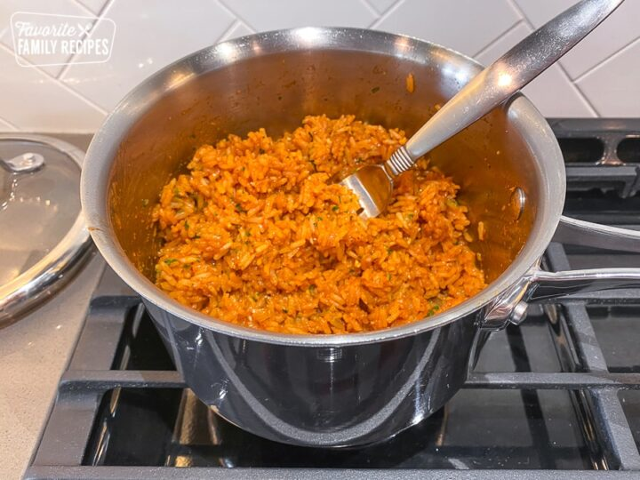 Mexican rice in a pot after being seasoned with spices and cilantro
