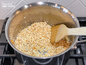 White rice being browned in a pot to make Mexican rice