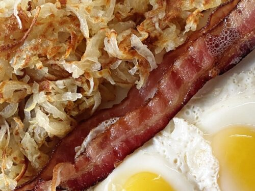 hash browns bacon and eggs on a plate