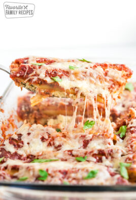 A piece of cheese manicotti being served out of a casserole dish