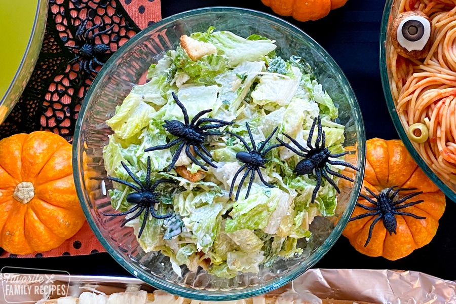 Halloween Caesar salad with spiders in the bowl