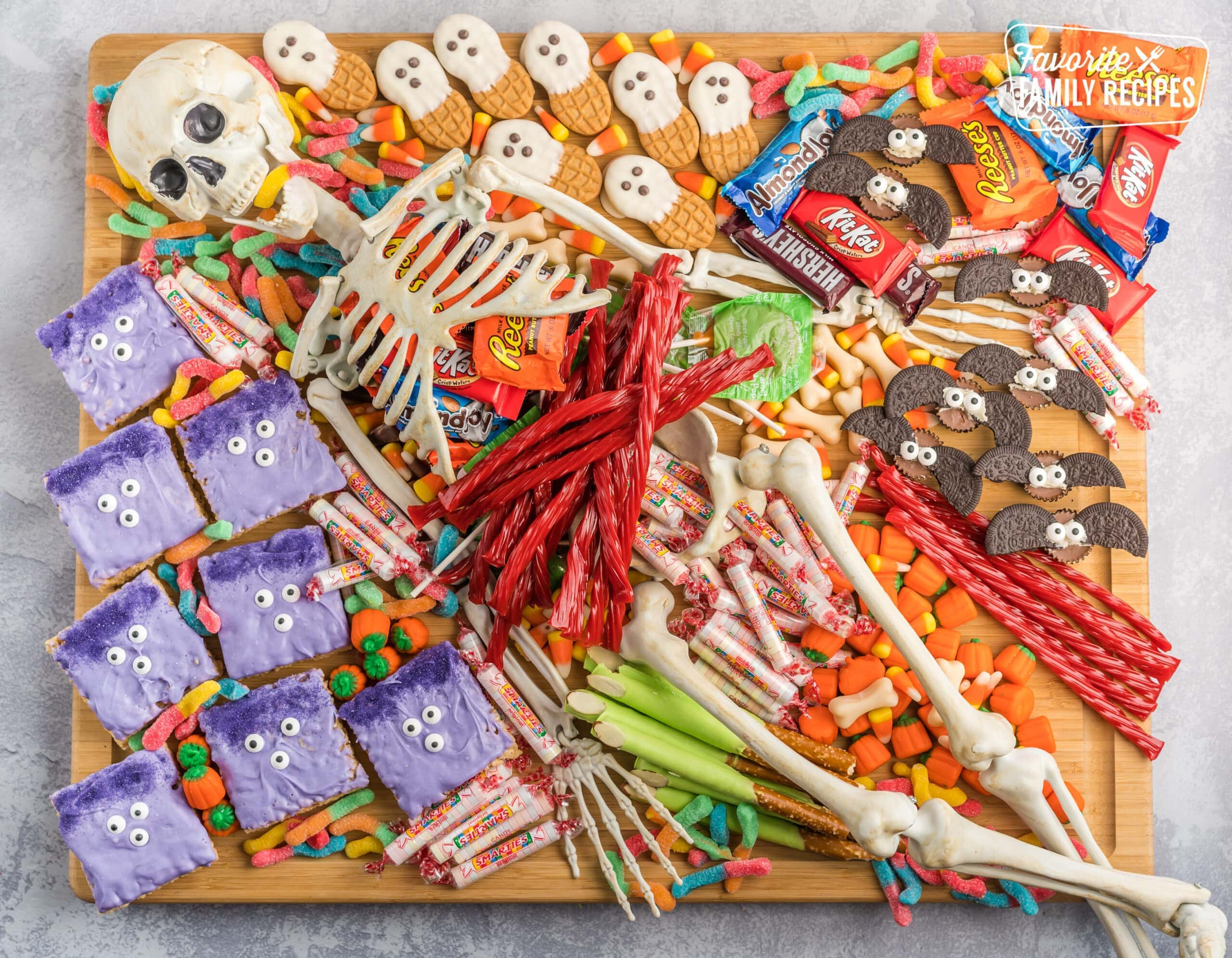 A halloween charcuterie board covered in candy and spooky treats with a skeleton in the middle.