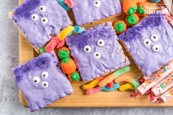 Monsters made out of Rice Krispie Treats dipped in purple chocolate with candy eyes and sprinkles for hair.