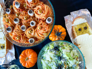 Halloween spaghetti in a bowl with salad and cheesy garlic bread