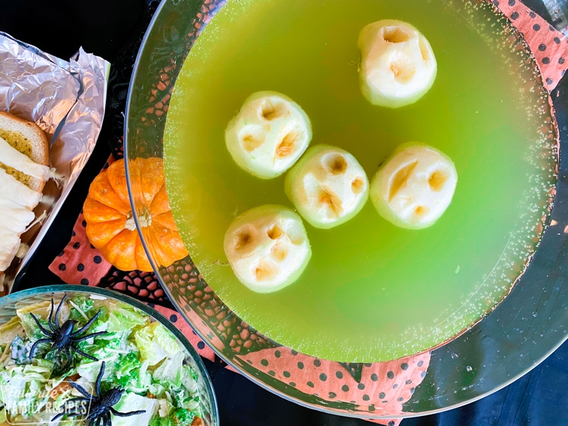 Green punch with apples carved to look like shrunken heads