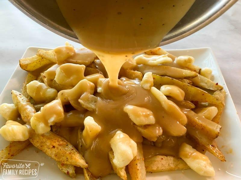 poutine gravy being poured onto fries