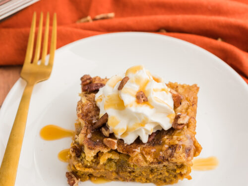 Pumpkin cobbler on a plate topped with whipped cream, caramel sauce, and pecans