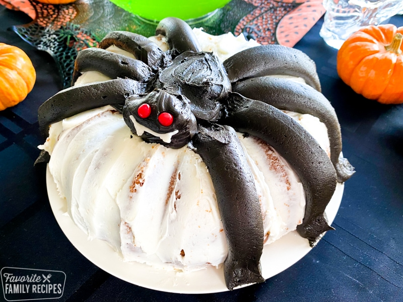 pumpkin bundt cake with giant black frosting spider in the middle