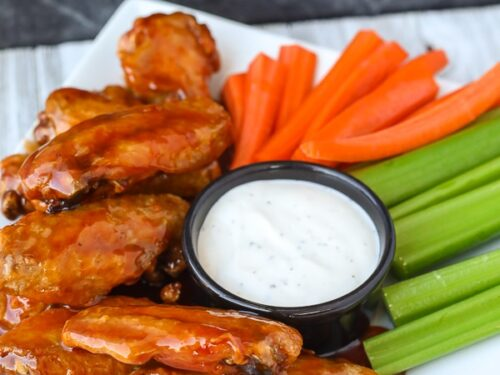 Portrait view of air fryer chicken wings on a plate with veggies and ranch dip