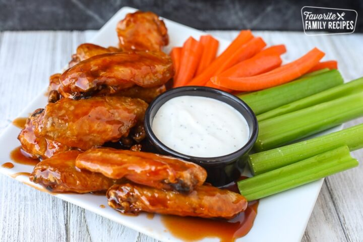 Side view of air fryer chicken wings on a plate with veggies and ranch dip