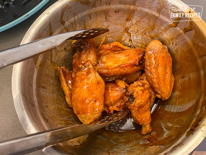 Chicken wings being tossed in a bowl with sauce