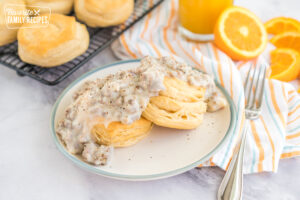 Two biscuits on a plate topped with sausage gravy