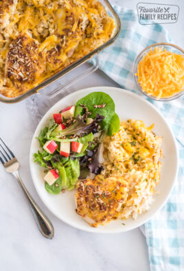 Chicken and Rice Casserole on a plate with some salad and the casserole dish in the background