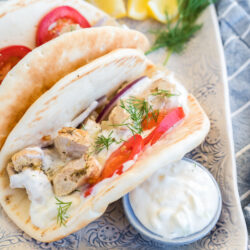 Two chicken gyros on a plate with a dish of tzatziki sauce, lemons, and dill