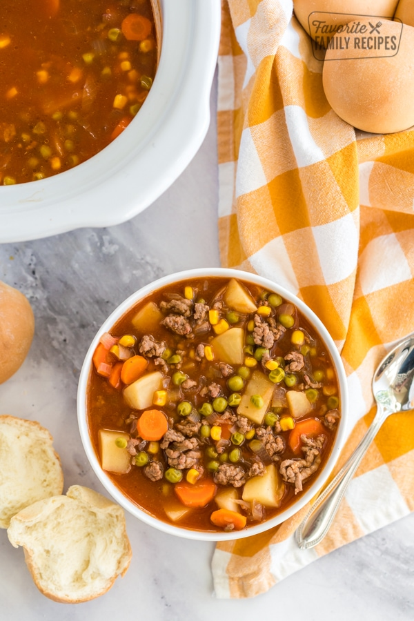 A bowl of crock pot vegetable beef stew with rolls and a crock pot in the background