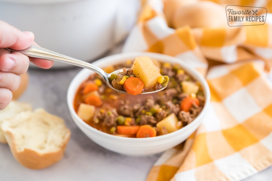 A spoonful of crock pot vegetable beef soup with a bowl and a crock pot in the background