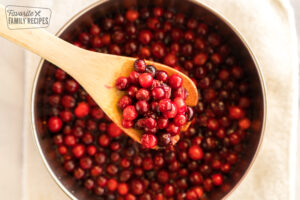 Fresh cranberries cooking in a saucepan to make cranberry orange sauce