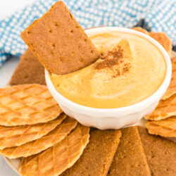 a graham cracker being dipped in pumpkin dip