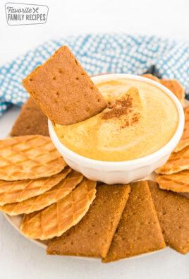 a graham cracker being dipped in pumpkin dip
