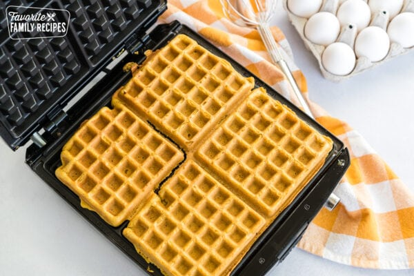 pumpkin waffles cooking in a waffle iron