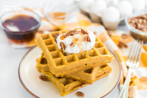 A stack of pumpkin waffles on a plate with whipped cream, pecans, and syrup