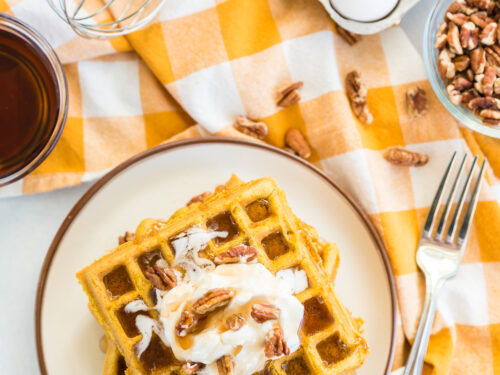 A stack of pumpkin waffles topped with whipped cream, pecans, and syrup.