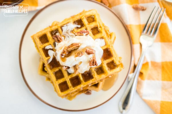 Pumpkin waffles with maple syrup drizzling down them