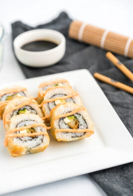 shrimp tempura rolls on a plate with soy sauce and chopsticks