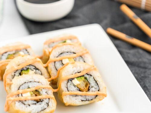 shrimp tempura rolls on a plate with soy sauce and chopsticks