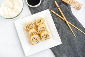 Shrimp tempura godzilla roll on a plate with chopsticks